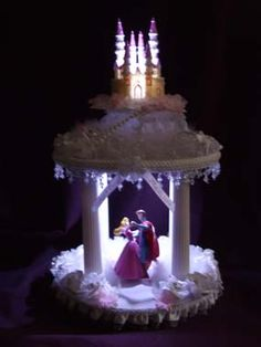"""2 Tier Sleeping Beauty & Prince Phillip Fairytale -  Each tier is attached to an 8"""" cake plate. The bottom tier can also have columns added, to suspend the entire 2 tiers above your cake. The 2 tiers together measure 15"""" tall with an 8"""" diameter. - The bottom tier features Sleeping Beauty & Prince Phillip having their first dance together in a fairytale cloud of marabou feathers... The path to the enchanted couples dance floor is lined with faux pearls. The couple is illuminated by light ."""