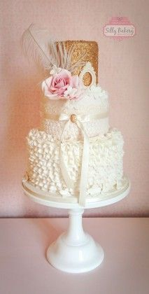vintage white and glitter ruffled wedding cake with feather