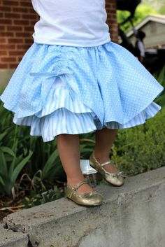 Circle skirt gathered with a casing and ribbon down one side to reveal a ruffled underskirt