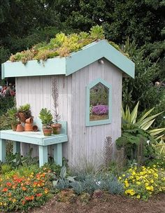 Succulent garden on top of a small shed with a mirror posing as a window. No details from site.