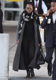 Laid-back: Lupita Nyong'o looked comfortable in a fitted black T-shirt and coordinating trousers as she arrived at JFK airport on Friday following the London premiere of Star Wars