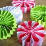Flowers from paper strips! Would be cute on wrapped presents or frames and baskets or a wreath made of a bunch of them.