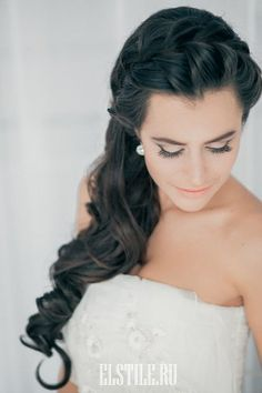 A long tousled hairstyle with a braided crown and a side-swept gathering of romantic waves.