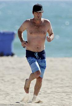 Med atletisk krop på stranden