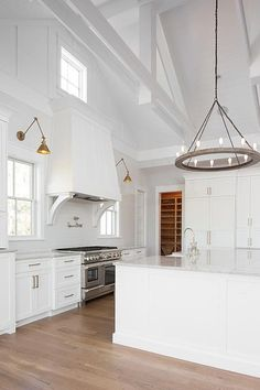 Stunning large white transitional kitchen featuring vaulted truss ceiling with a wood and iron ring chandelier.