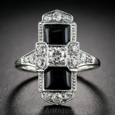 Art Deco Onyx and Diamond Dinner Ring. A striking and dramatic dinner ring from the 1920s, rendered in classic Art Deco colors: black (onyx) & white (diamonds). This sophisticated jewel, crafted in platinum and 18 karat white gold, sparkles with 15 old-cut diamonds set in a sleek tonneau shape design measuring 7/8 inch long.