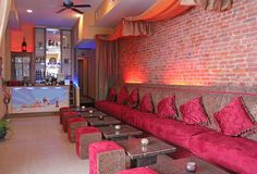 Hookah lounge design ideas - nice with the velvet seats, and ceiling drapery.