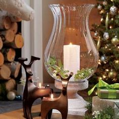 "Chalet Hurricane  Creates the air of a rustic retreat, your own warm and cozy cocoon in the winter woods. Light a pillar candle, sold separately, to add a warm glow to the blown glass shade. A distressed, bleached finish updates the faux wood resin base. 19""h, 10""w."