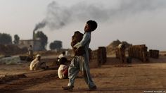 A Pakistani boy, Mozamal Omar, nine, who works in a brick factory, carries clay as part of his daily work, on the outskirts of Islamabad.
