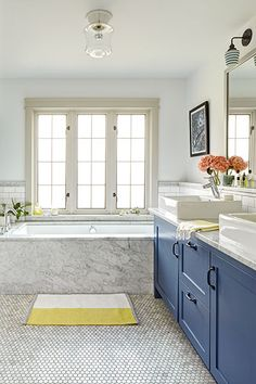 Slab Carrara marble surrounds the tub's top and side and extends up to the windows, where it forms a waterproof ledge. Honed marble hex floors, a marble vanity top, and a custom marble pencil ledge encircling this bathroom give the space a unified look.