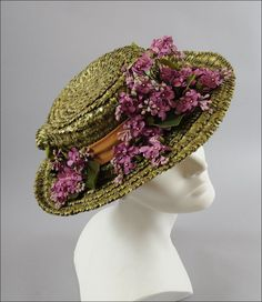 1950's olive green straw hat with lilac flower trim (side view) | Olive green straw in a very textured weave. The straw creates a bow in the back. The hat has a band in an apricot tone