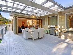 Outdoor living area of large deck with covered pergola in laserlight.  Bi-Fold doors open up from the kitchen to the deck for easy entertaining
