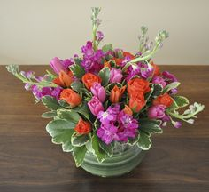 Cheery flower arrangement in bright colors - with tulips, african spray roses, stock and pitt.