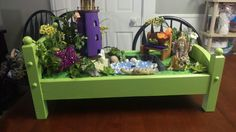 A doll bed turned into an awesome fairy garden with pond element.