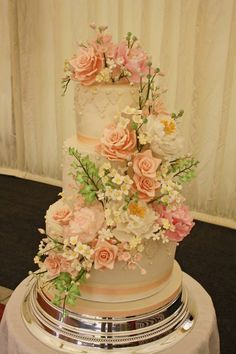 Cascading peonies, roses and hydrangea flowers on a three tier wedding cake, in pink, peach and white.