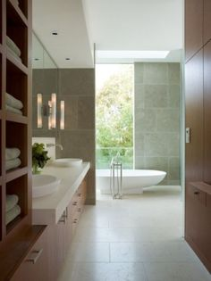 Although this wall and floor tile feel a bit cold to me I love the warmth of the woodwork, the glazing/natural lighting, the floating vanitity, wall faucets and especially the Lacava tub. Yummy!