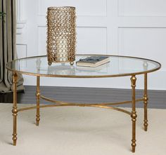 The beautiful glass coffee table features an oval top of clear tempered glass inset within a gold-leafed, forged iron frame. This elegant design makes a statement in any home or office and its regal s