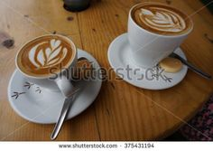 Two cappuccinos on cups on wooden table.