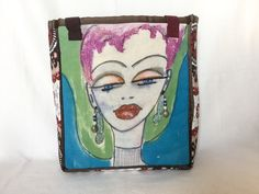 """Wanda - Because Your Eyes Should Tell A Story This bag measures 13"""" wide by 16"""" high by 6"""" deep The image is painted and dyed on linen Wanda has a pair faux pearl and bead dangling earrings The back and sides are a beautiful pattern in brown, beige and red The lining is shiny gray A 5"""" x 7"""" open side pocket All seams are tailored with pretty brown ribbon 9"""" multi-colored woven straps"""