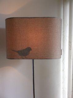 Silhouet van vogeltje achter lampenkap geplakt.