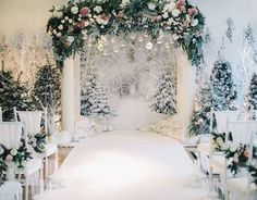 all-white wedding ceremony space with fir trees and hanging ornaments