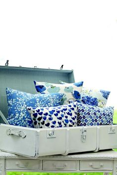 Lovely designs of #romo, poppies and blue!! white suitcase painted to hold blue pillows in bedroom www.tecninovatextile.com