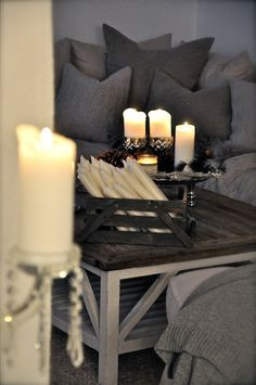 A cosy grey sofa with knitted cushions surrounded by candles.