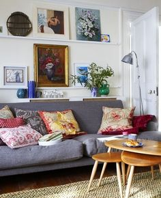 grey sofa with jute rug, colorful vases, nesting wood tables