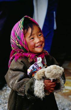 Tibet-little girl loving her teddy bear.