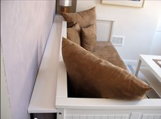 """A strip of MDF, painted white, and used as a """"shelf"""" to hide the extra mattress for Ikea Hemnes daybed (stored behind)."""