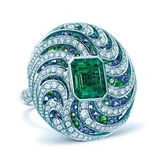 Ring of an emerald-cut emerald with round blue sapphires, tsavorites and diamonds.