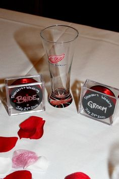 For the head table I made a hockey puck for each member of the wedding party with their names on it and hot glued red ribbon around it. I got the hockey puck display boxes from a local sport store for around 1 $ each. The writing was done with a silver metallic sharpie and for the girls pucks I put rhinestone stickers on them. They all loved them and made the head table look awesome!