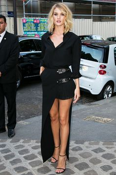 Rosie Huntington-Whiteley wears a black button-down top, pleated high-low skirt, and Stuart Weitzman sandals