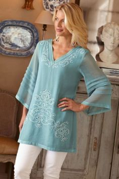 Elegant tunic with cutwork embroidery and pleated sheer bell sleeves.
