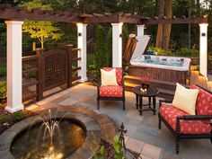 Multiple water features combine in this Minnesota patio with a pergola: a water fountain, hot tub and an outdoor shower. The fountain, which has underwater lighting, and flooring are made of New York bluestone. The pergola is made of fiberglass columns, cedar timbers and wood beam rafters. The outdoor shower was added by Southview Design in the second phase.