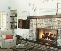 Brick fireplace with reclaimed wood sitting hearth  and mantle and shiplap walls