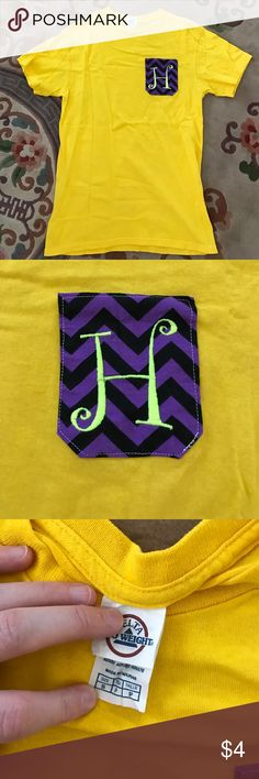 "DONATING 7/1🌟Gold Monogram Tee This is a size small monogrammed t-shirt with an ""H"" in the upper left hand corner of the front. The letter is like green and placed on a pocket like purple and black zigzag pattern. I bought this shirt and only wore it once. It's super cute for someone who's name starts with the letter H! Back of shirt is plain and there are no rips, holes, or stains! Gildan Tops Tees - Short Sleeve"
