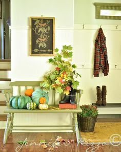 Boots filled with leaves and blue and orange pumpkins add warmth to this front entry.