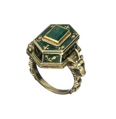 "This fantastic Victorian ""poison ring"" is 18k gold, with a central casket flanked by two ram's heads. The casket, which is enameled in green and set with a large emerald, opens to reveal a sizeable inner chamber that would easily meet all your poison-storage needs."