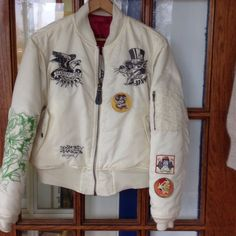 """Ed Hardy jacket Off white or cream with """"tattoos"""" stitched on jacket front,sleeves & back. Like new only worn once  jacked only comes to your waist Ed Hardy Jackets & Coats Puffers"""