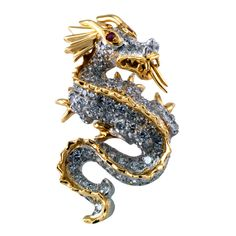 This cute fiery dragon pin, with an articulated tongue, bears a fierce expression. The eyes are rubies, bezel set, and the scales are formed by one hundred and one glittering diamonds, totaling appx 1ct. The back is fitted with a concealed bail for wearing as a pendant. Made in 18kt yellow gold and platinum.