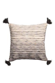 Capa de almofada em tecido flammé de mistura de algodão com fios brilhantes na frente. Parte de trás em tecido de algodão de cor lisa. Borlas nos cantos. Fe