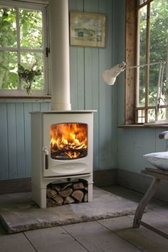 'rustic modern' free standing wood stove with room for wood underneath. By Charnwood (C series)