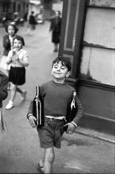 Henri Cartier Bresson is known as the father of photojournalism. look at the pride in his face that momma trusted him to go get the wine for the party or festival!