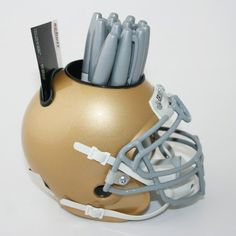 NOTRE DAME FIGHTING IRISH NCAA Football Helmet Desk Caddy by Schutt. $21.99. Authentic NCAA team logos and graphics!. Authentic metal facemask!. Built-in pockets for pens, pencils, and business cards!. Scaled 1/4 size of the authentic game-day helmet!. Think a caddy is just for the golf course? No duffer in plaid pants ever looked as good as this Football Helmet Desk Caddy from Schutt Sports! This cool but functional desk caddy holds business cards, pens, pencils a...