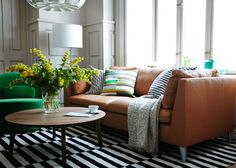 Lounge area with light brown leather sofa, green swivel easy chair and coffee table in walnut veneer- IKEA