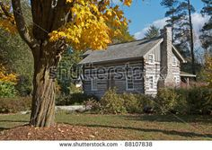 Small traditional early settler log cabin with colorful autumn maple tree in foreground. Horizontal format.