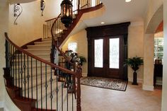 One of two wrought iron staircases, this one in the entry rises dramatically to a wide upstairs hallway that continues the circular design of the stairs and provides light from the second story windows.