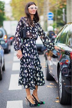 Giovanna Battaglia wears a black floral midi dress, shoulder bag, white sunglasses, and statement heels