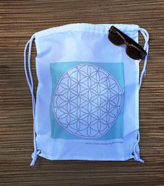 Flower of life unique designed beach drawstring bag for daily use. The drawstrings white bags are perfect as a a beach bag, yoga festival bag, eco market bag and much more! The white bag nylon sack comes in white basic color with the Sacred geometry patterns printed on the them making them an inspiring item to go around and help caring around all your stuff. This light backbags bags are also perfect for a gift to a woman friend, a yogagift, a teacher gift and also as a wedding giveaway! They…